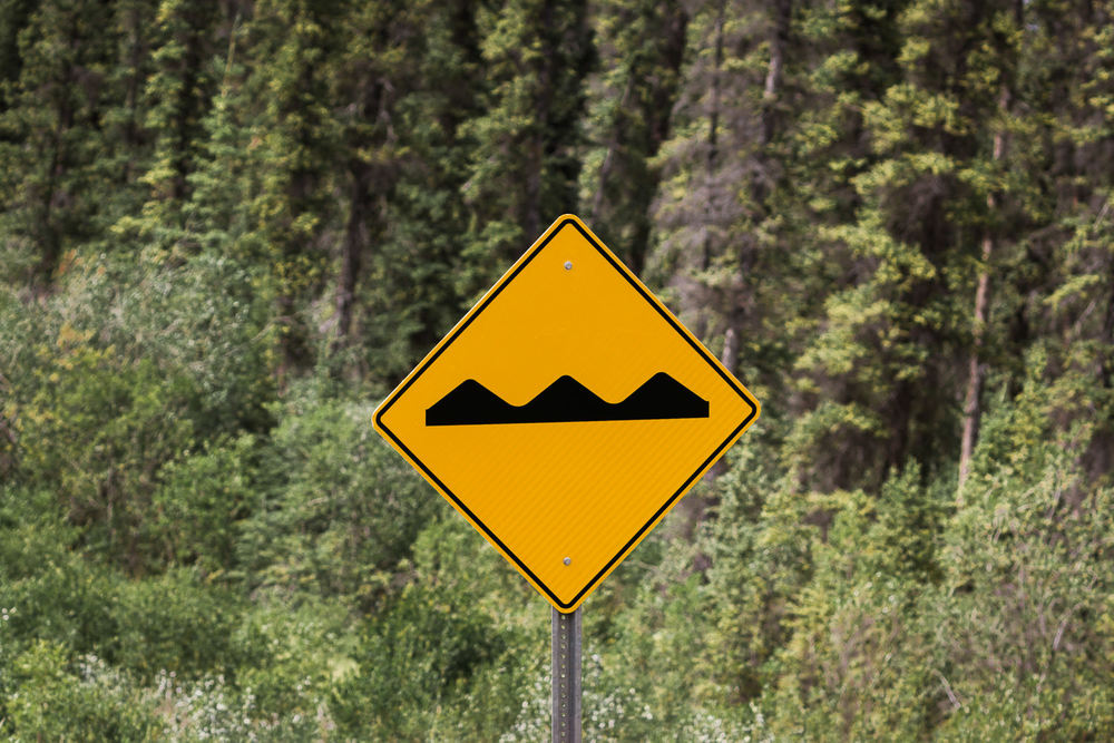 How I grew to dread this sign with the squiggles. We'd read about frost heaves during the planning process, but weren't prepared for the stress they'd bring to the driving experience.   Mother Nature really flexes her muscles with this phenomenon; she basically annihilates roads that sit atop permafrost, causing them to lift and buckle in really gnarly ways. Think speed bumps on steroids. We couldn't take our eyes off the road; while some areas of frost heaves were marked, many were not and you could easily rattle your car to the point of rendering it undrivable if you hit one too quickly.   The second (northern) half of the Cassiar is the portion that didn't see the dramatic improvement that we'd read about. The road narrows to one lane, shoulders and guardrails disappear and pavement becomes riddled with potholes and frost heaves. Top it off with some steep grades, switchbacks, stretches of gravel/dirt in lieu of concrete and 35 mph becomes your top speed. Needless to say, this portion along with several stretches of rough road on the Alcan made for some challenging driving.