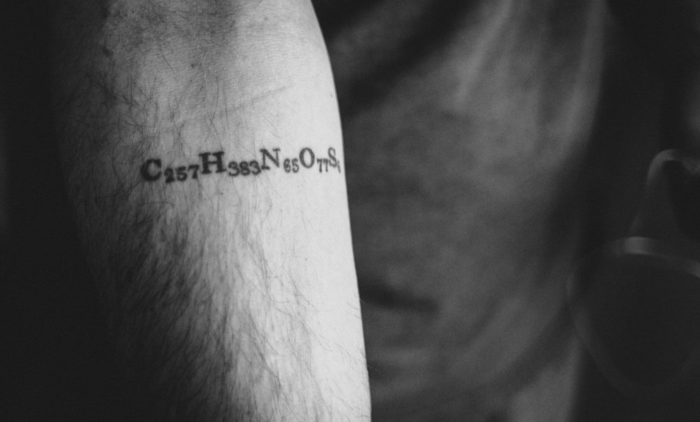 A small tattoo on Tom's right forearm with big meaning. It's an homage to his lifeblood; C257H383N65O77S6 is the chemical formula for the synthetic insulin he has taken for the majority of his life.