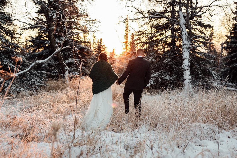 Bride and groom enjoying winter sunset in Alaska