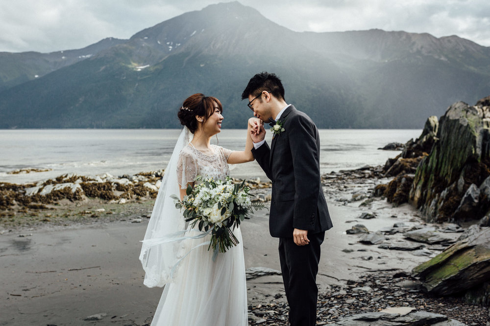 Groom kissing his bride's hand in front of misty mountains