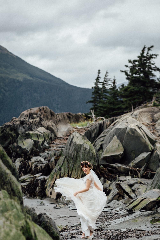 Bride twirling dress on rocky Alaskan beach