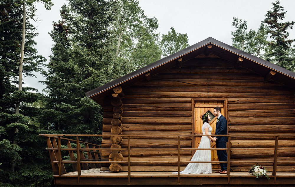 Couple holding hands in front of Alaskan log cabin