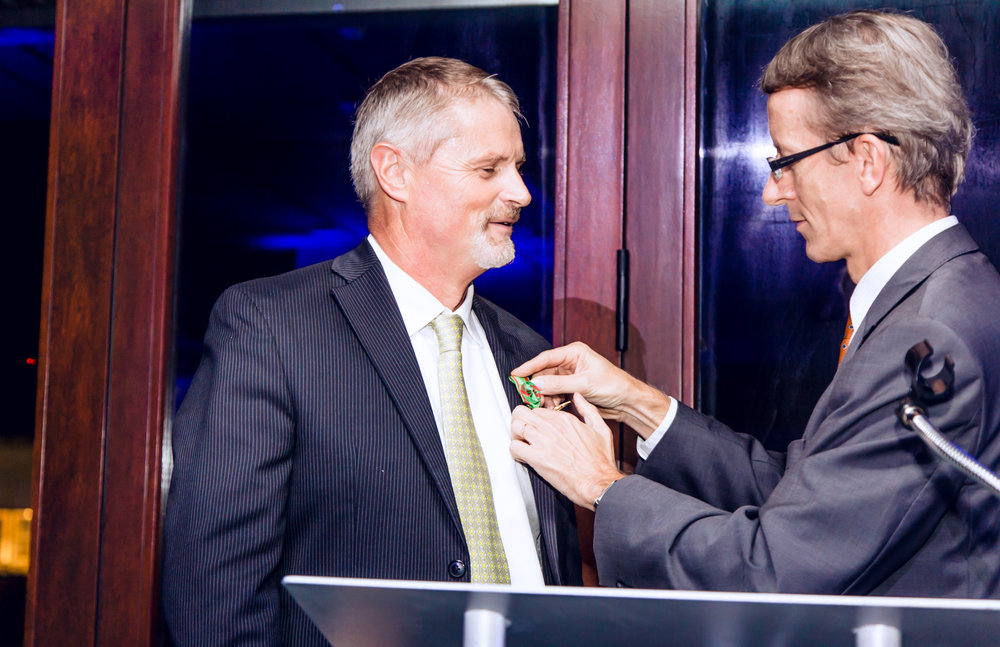 Thierry Isambert receiving the Ordre Du Mérite Agricole award from Consul General, Philippe Letrilliart at Palm Court Event Space in the Miami Design District