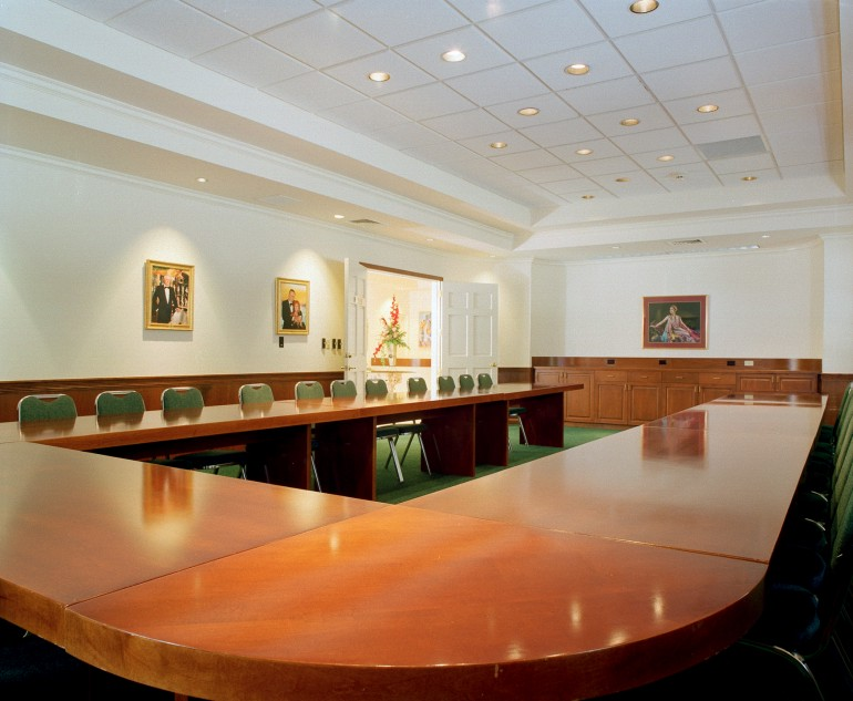 The wood-paneled ,  board room on the first floor accommodates 50 people comfortably. There is a ceiling recessed slide screen, a built-in buffet, and modular conference tables.