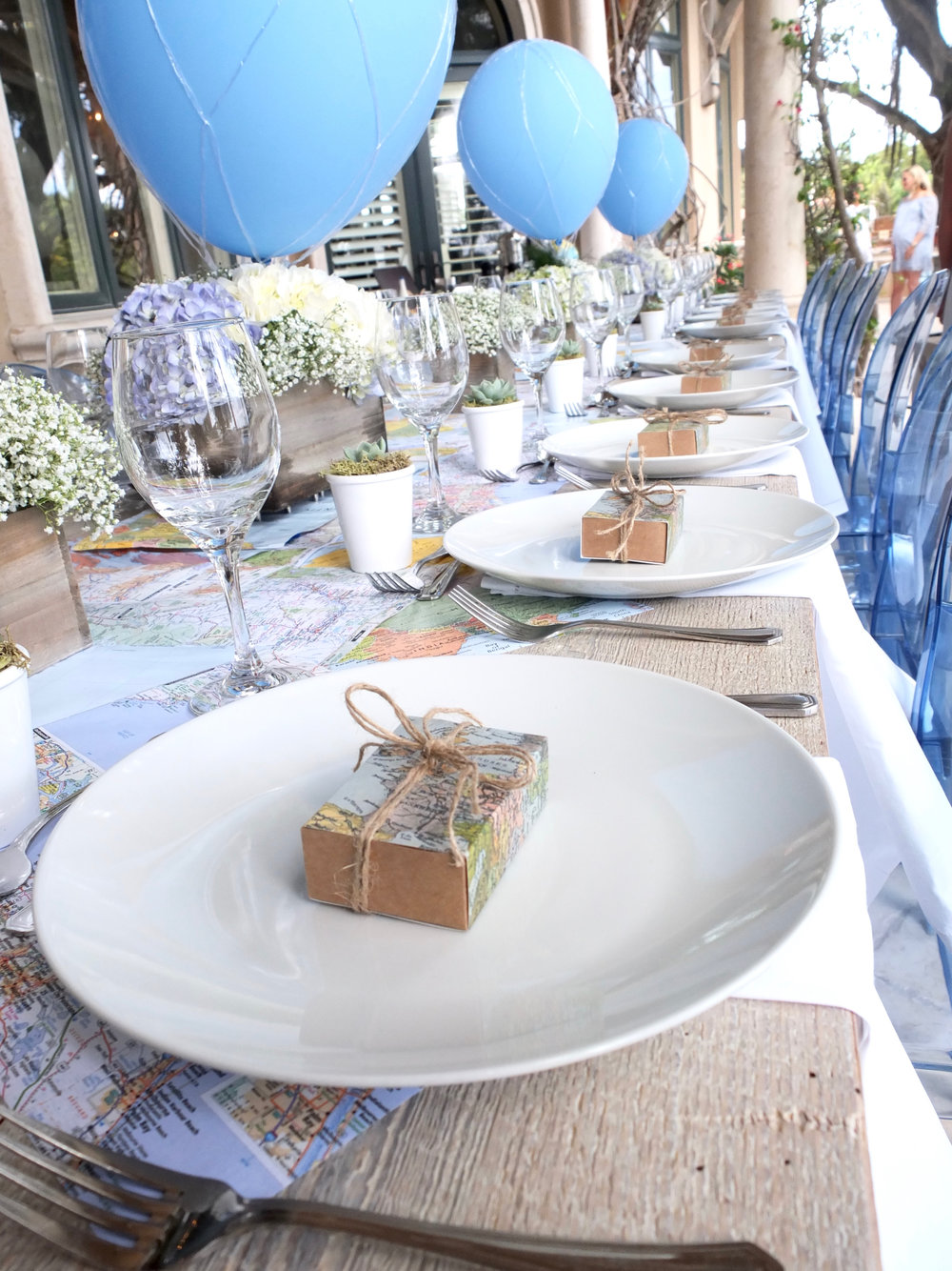 Arrangements of pale blue hydrangeas and Baby Breath, in small wooden crates from Unearthed Vintage, were the table centerpieces, along with blue balloons styled as hot-air balloons for the travel theme. The tables are made from 100 year-old reclaimed pine. [Photos: Nicky Monteiro]