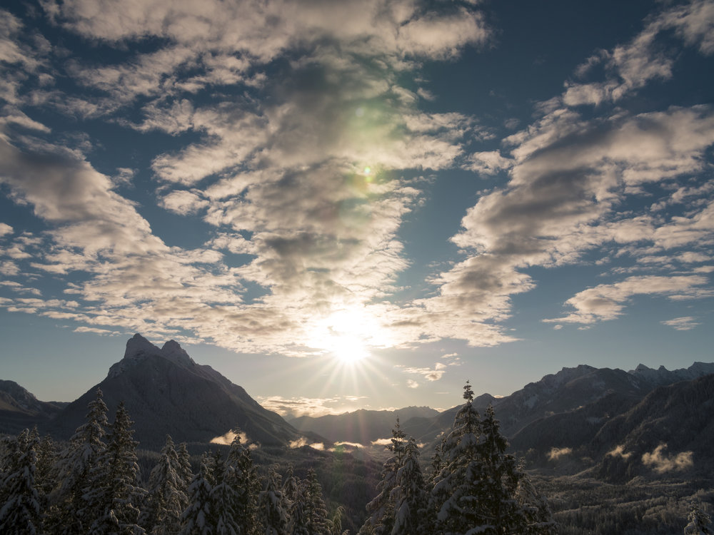 Scattered Clouds Above Snow Covered Mountain Valley Landscape with Beautiful Sun Flare