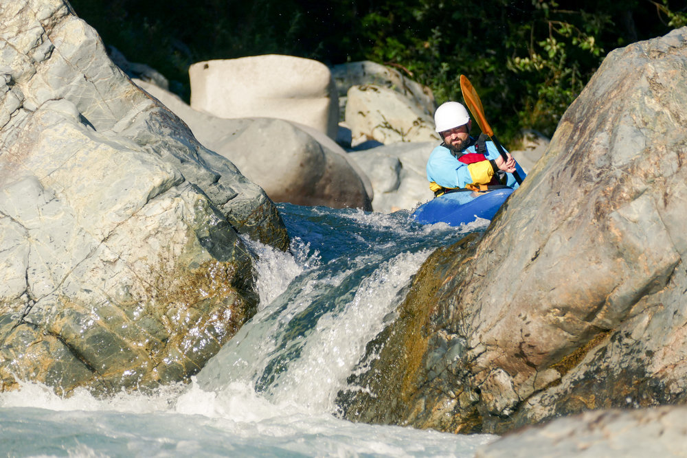 Man_on_Kayak_Facing_Rocky_Rapids_Paddling_Toward_Waterfall_Drop.jpg