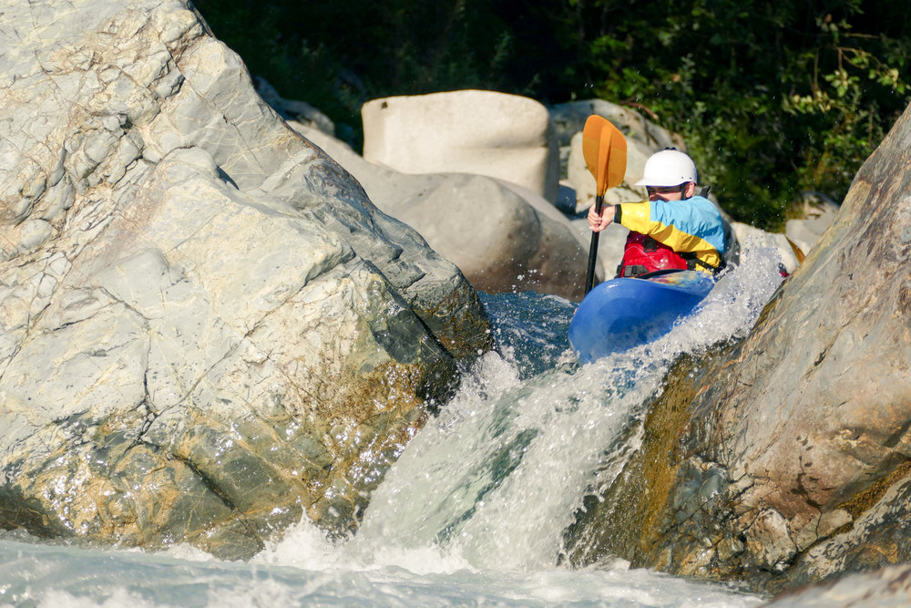 Extreme_Kayaker_Going_Over_Rocky_Waterfall_Drop_in_Raging_River_Rapids.jpg
