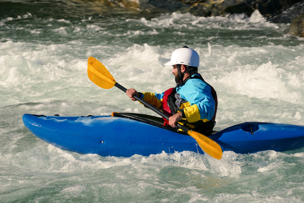 Side_Profile_of_Extreme_Kayaker_Paddling_in_Raging_River_of_White_Water_Rapids.jpg