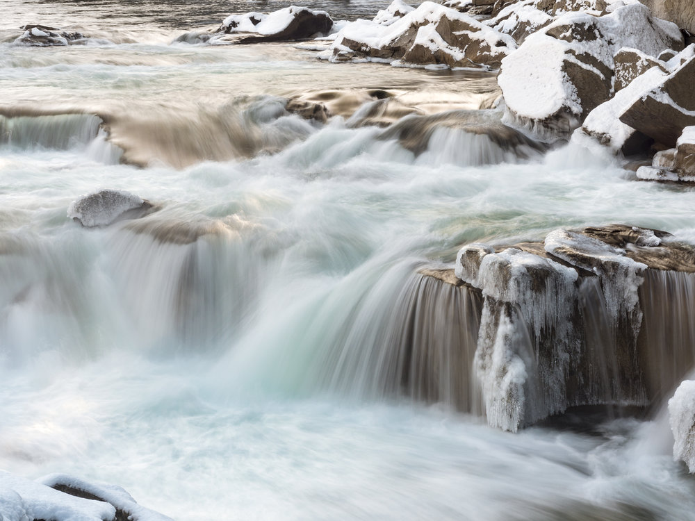 River Rapids Flowing with Fluid Motion in Winter with Snow and Icicles