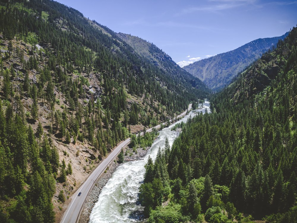 Aerial_of_Scenic_Wilderness_Highway_by_Mountain_River.jpeg