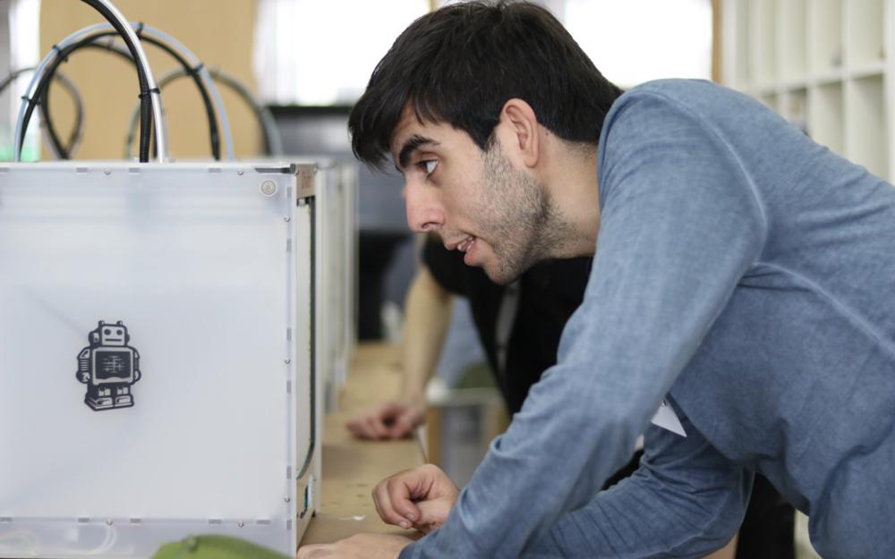 Een student bekijkt de voortgang van zijn 3D-printopdracht tijdens een hackathon. Foto: Berry Groenendijk.