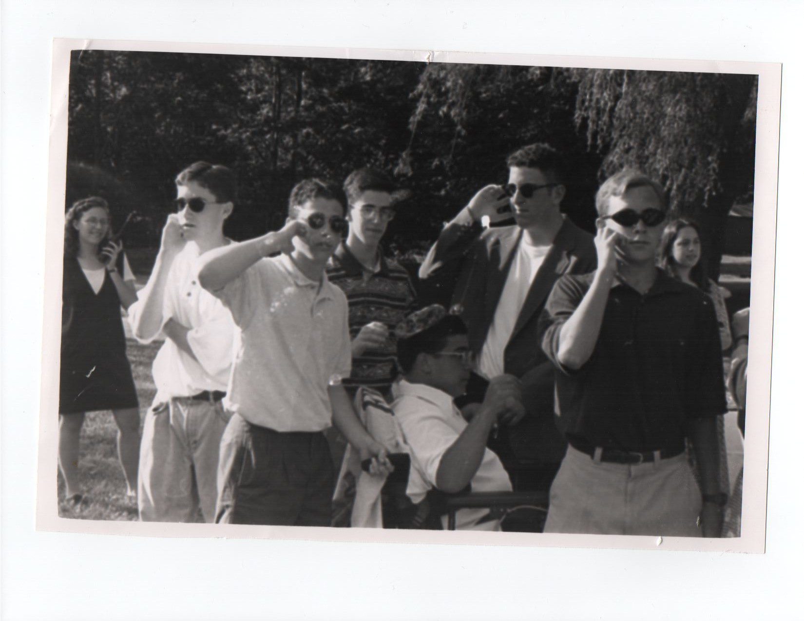 Outdoor scene featuring 14-year-old Matan sitting in a power wheelchair flanked by for male teenagers, well dressed in dark sunglasses, touching imaginary Secret Service ear pieces. The camp program director can be seen on one side, holding a walkie-talkie with a bright smile. Also pictured, one teenage male not in uniform, And one teenage female, identity unknown