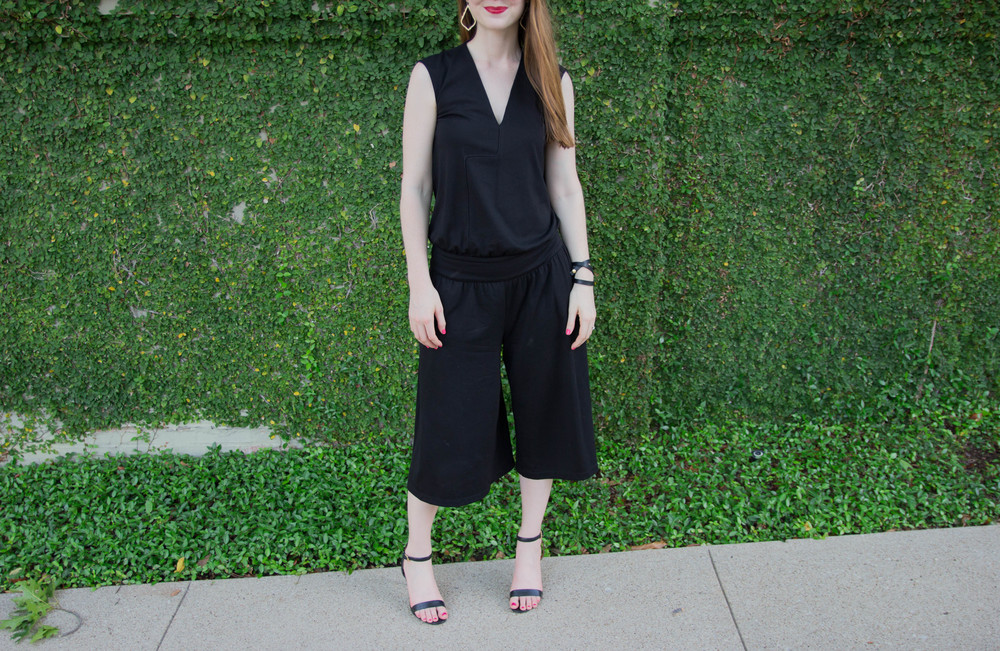 cultro clothing, nyc. black culotte jumpsuit, karen walker sunglasses, tory burch strappy sandal,