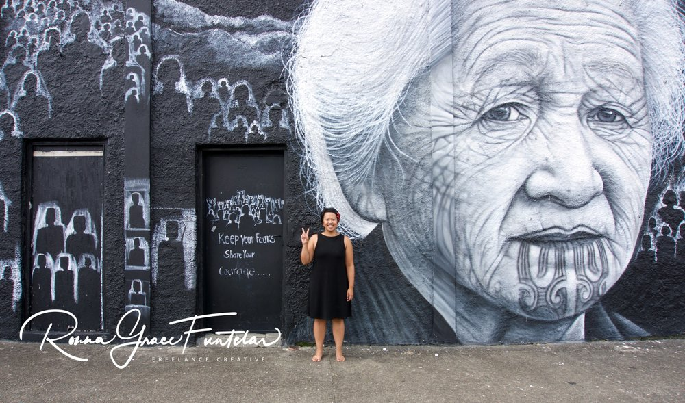 Standing in front of the street art by artists Owen Dippie and Tame Iti.