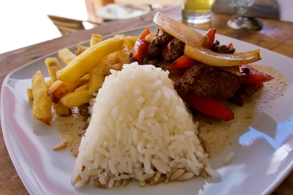 Lomo Saltado is served with papas fritas (hot chips) and rice.