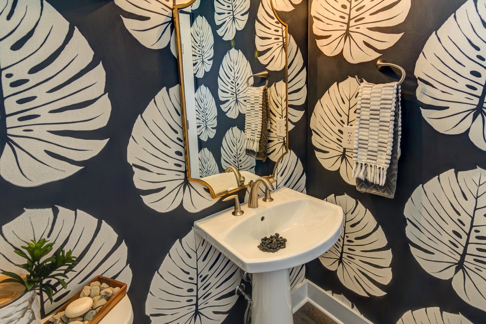 Black and white textured wallpaper adorns the powder bath in the Sycamore model.