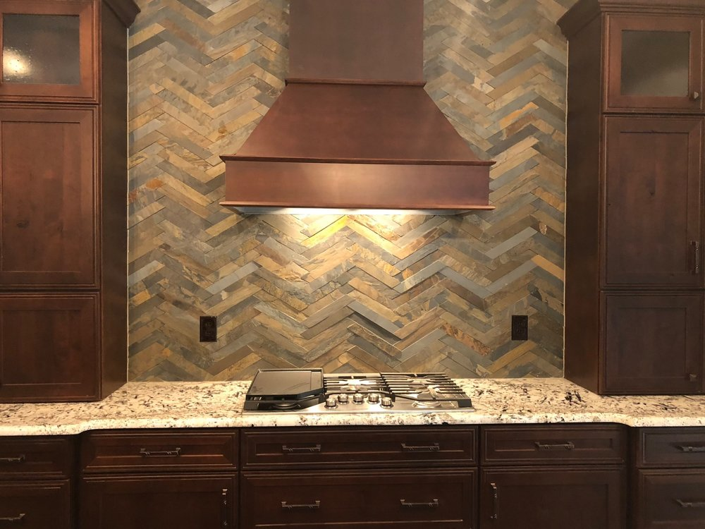 This natural stone backsplash creates a rustic feel throughout this kitchen.