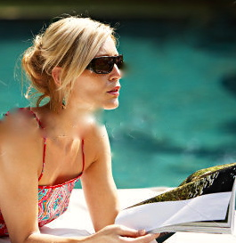 stock-photo-fashionable-attractive-woman-lounging-by-a-swimming-pool-reading-a-magazine-and-wearing-shades-110118377