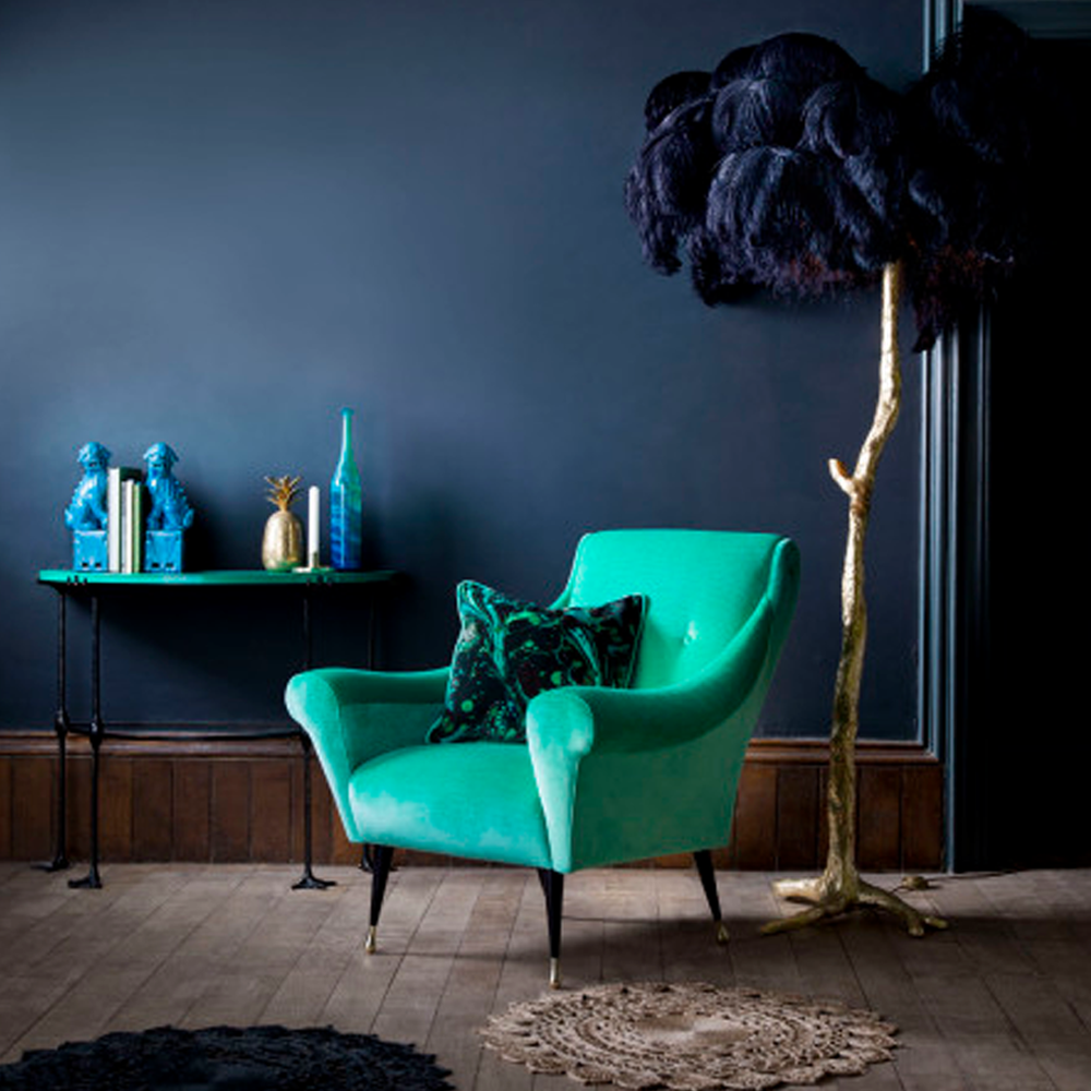 Inky blues and earthy tones set the scene in showcasing the green armchair from Matthew Williamson's new furniture collection. Complementary shades of blue and gold are uses to style the set.   Image:  Matthew WIlliamson