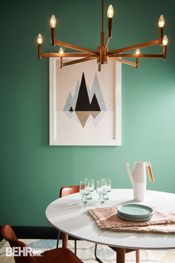 The gorgeous green wall is the star of the show in this calming dining space forming the perfect backdrop to let the artwork, stunning light fixture and table setting shine.  Image:  Pinterest
