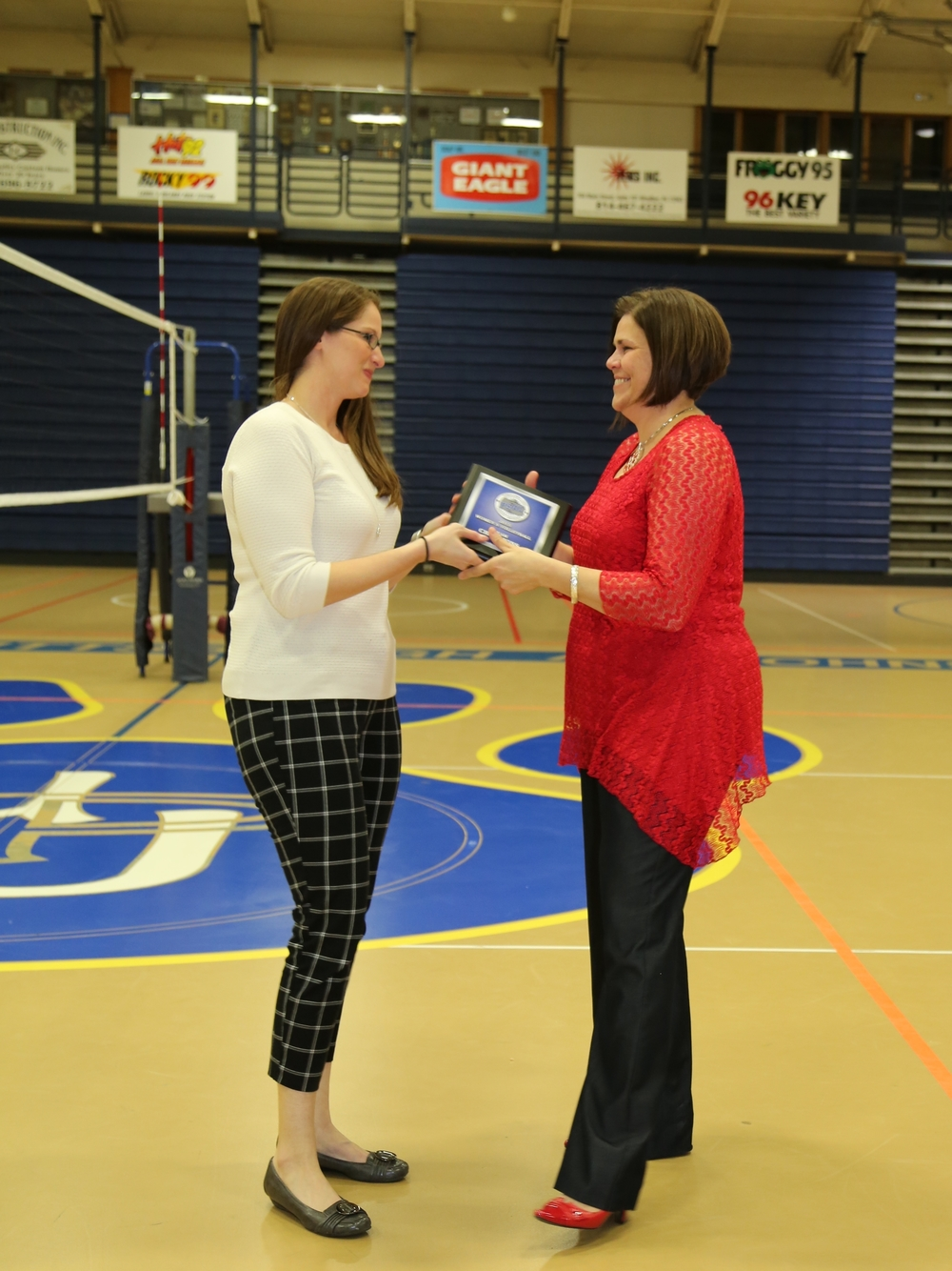Head volleyball coach Leanne Piscotty (right) receives her Pennsylvania State Athletic Conference (PSAC) Championship plaque from Carlin Chesick, PSAC associate commissioner.