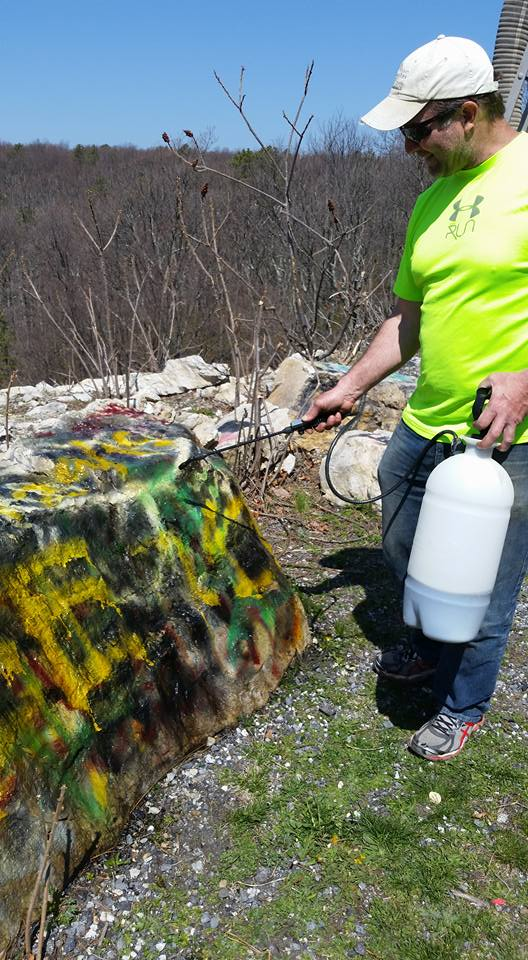 A volunteer removes graffiti from rocks in Michaux State Forest.