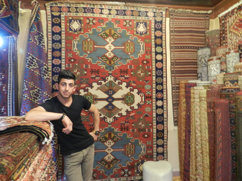 Saddam posing with his tapestries