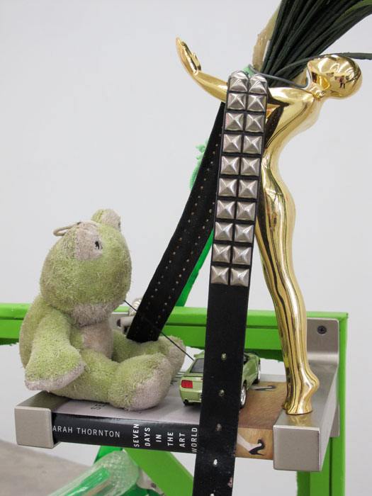 Justin Lieberman,  The Green Party Monument with Bookshelf  (detail), 2011, wood, aluminum, studded belt, brass candle stick, resin, brick, pipe, frog, car, brass statue, champagne flutes, 65 x 54 x 32 in