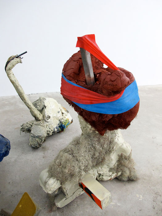 Jo Nigoghossian,  Stomps, aka Spito , 2011, cast concrete, wood, spray paint, fake hair, steel, elastic, burlap, 47 x 31 x 25 in