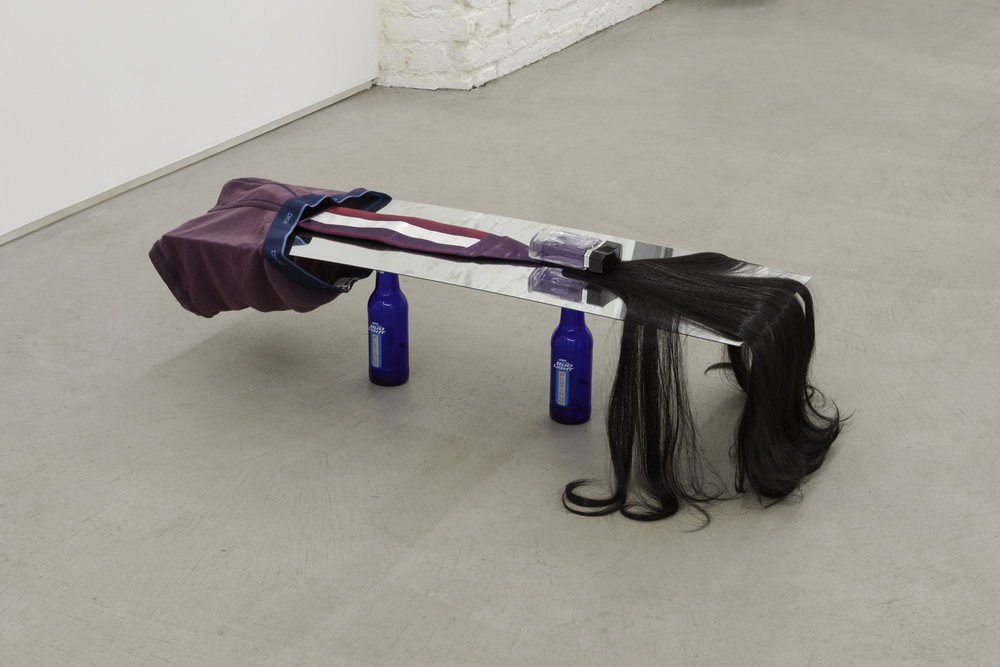 Kayode Ojo,  Untitled , 2013, Bud Light Platinum bottles, mirror, DKNY underwear bleached at Le Bain, cummerbund, King of Rap cologne, Yaki Pony synthetic hair, 10 × 38 × 12 in.