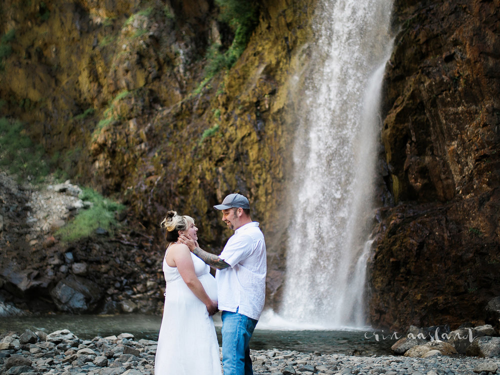 couple embracing next to waterfall maternity barefoot