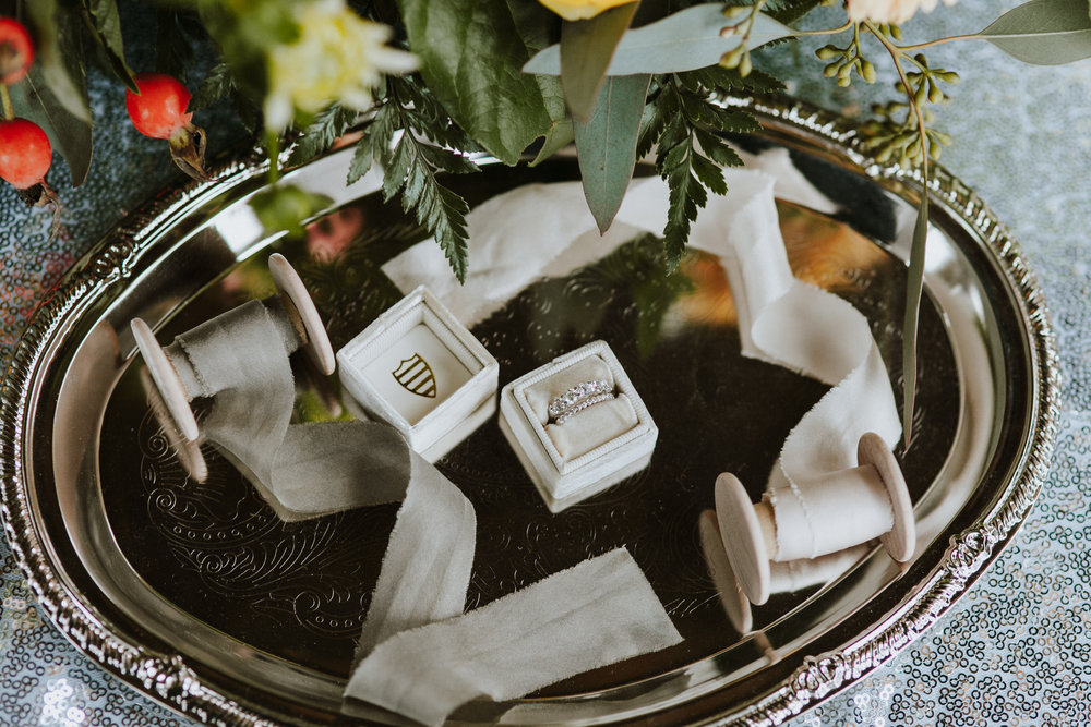 Wedding rings and flowers, spools of ribbon