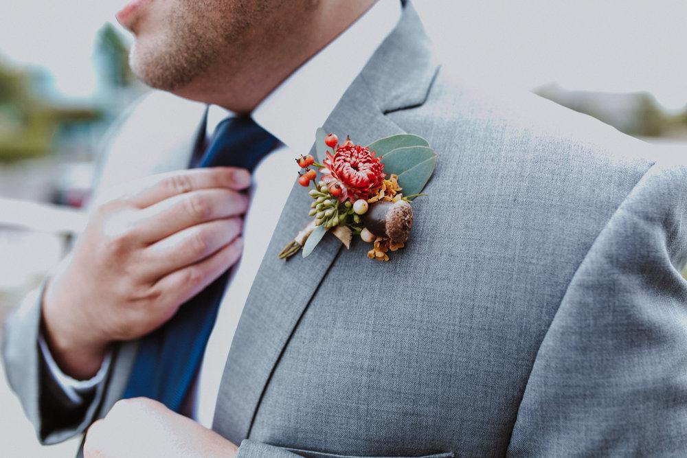 groom adjusting tie, grey suit navy tie