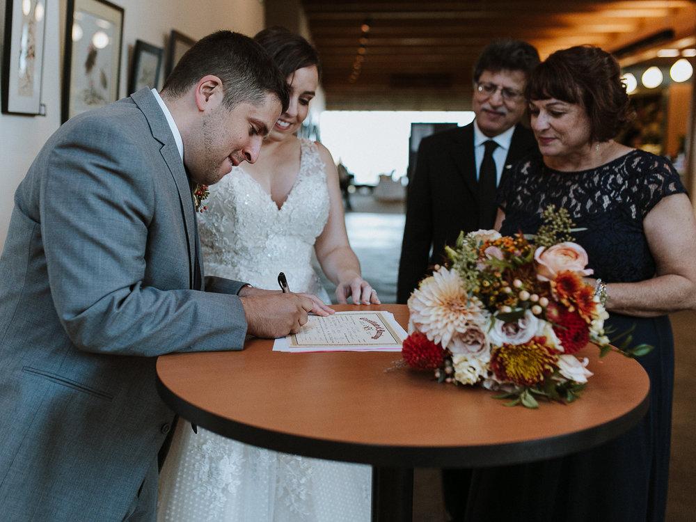 Erin Aasland wedding Photographer bride and groom signing marriage certificate