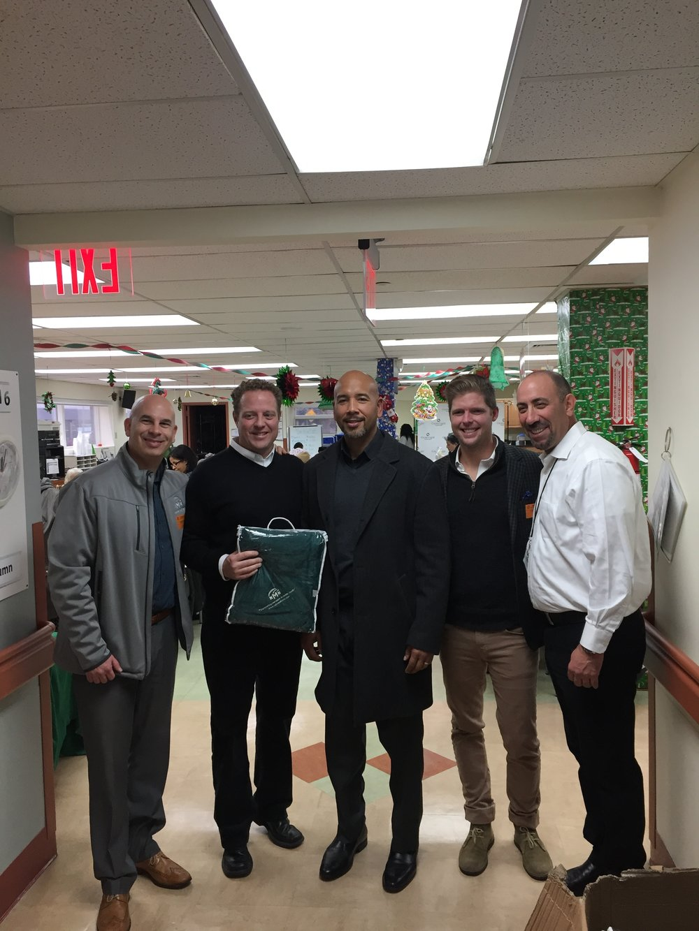 Members of National MedTrans executive team at a recent NMN Cares event donating blankets to members.  Bronx Borough President, Rubén Díaz Jr., also participated in the event.  From left to right: Andrew Winakor (CEO), Steve Wilson, (CXO), Rubén Díaz Jr. (Bronx Borough President), Billy McKee (President), Greg Billing (EVP)