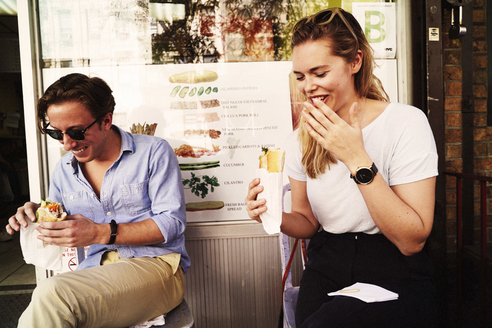 Boy and girl laughing while eating Banh Mi.jpg