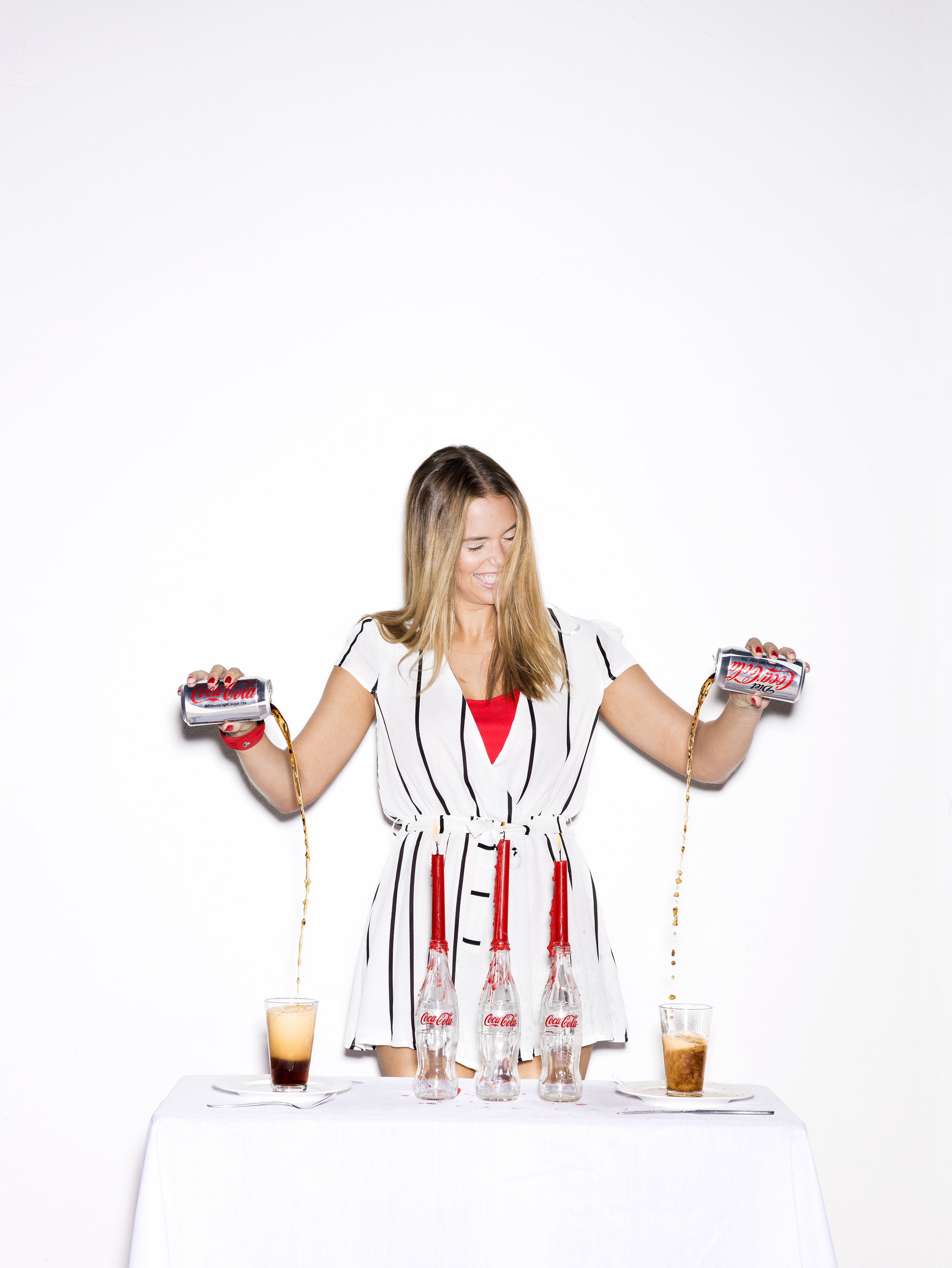 Girl pouring diet coke into glasses.