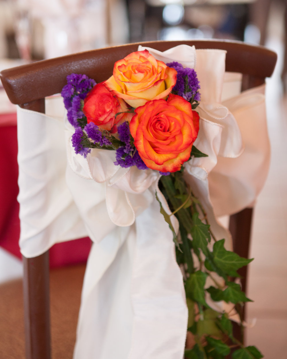wedding reception chair bow with floral accent white red orange purple.jpg