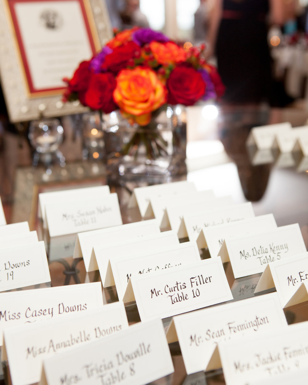 wedding reception place cards table flowers red orange purple.jpg