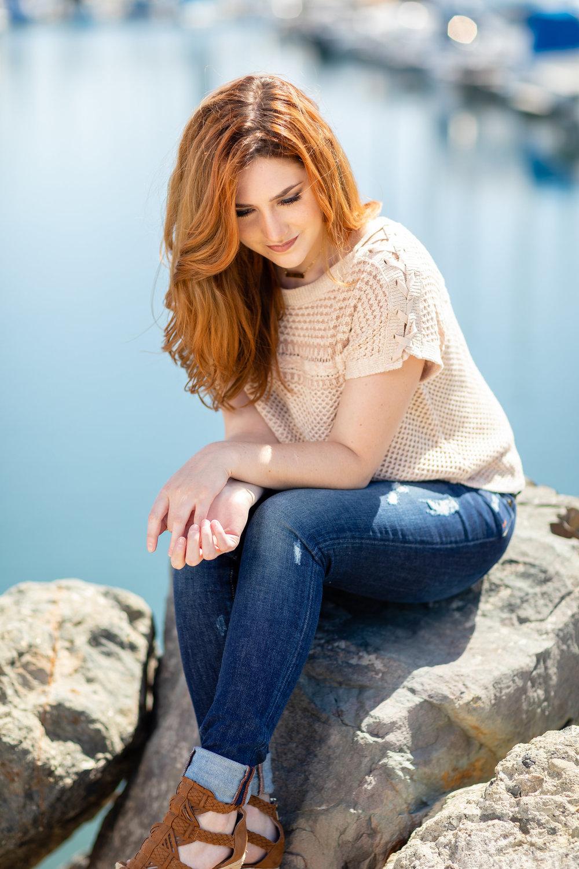 Woman sitting on rocks along the harbor.jpg