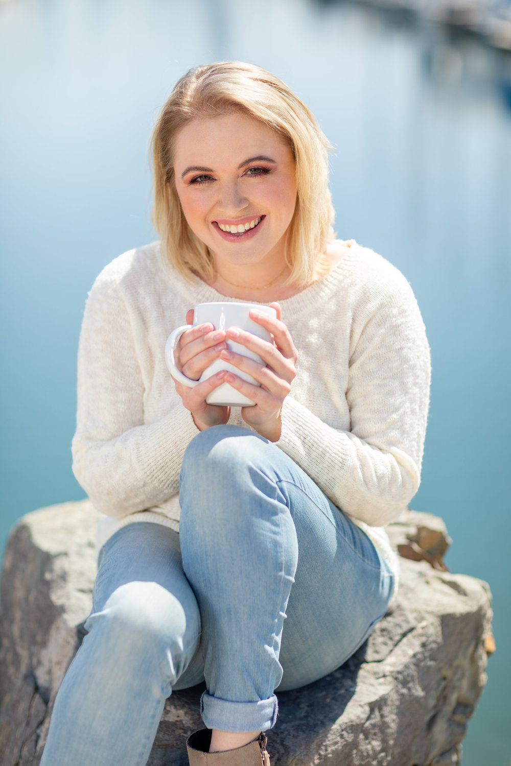 Female blonde in white sweater sitting on the rocks with coffee.jpg