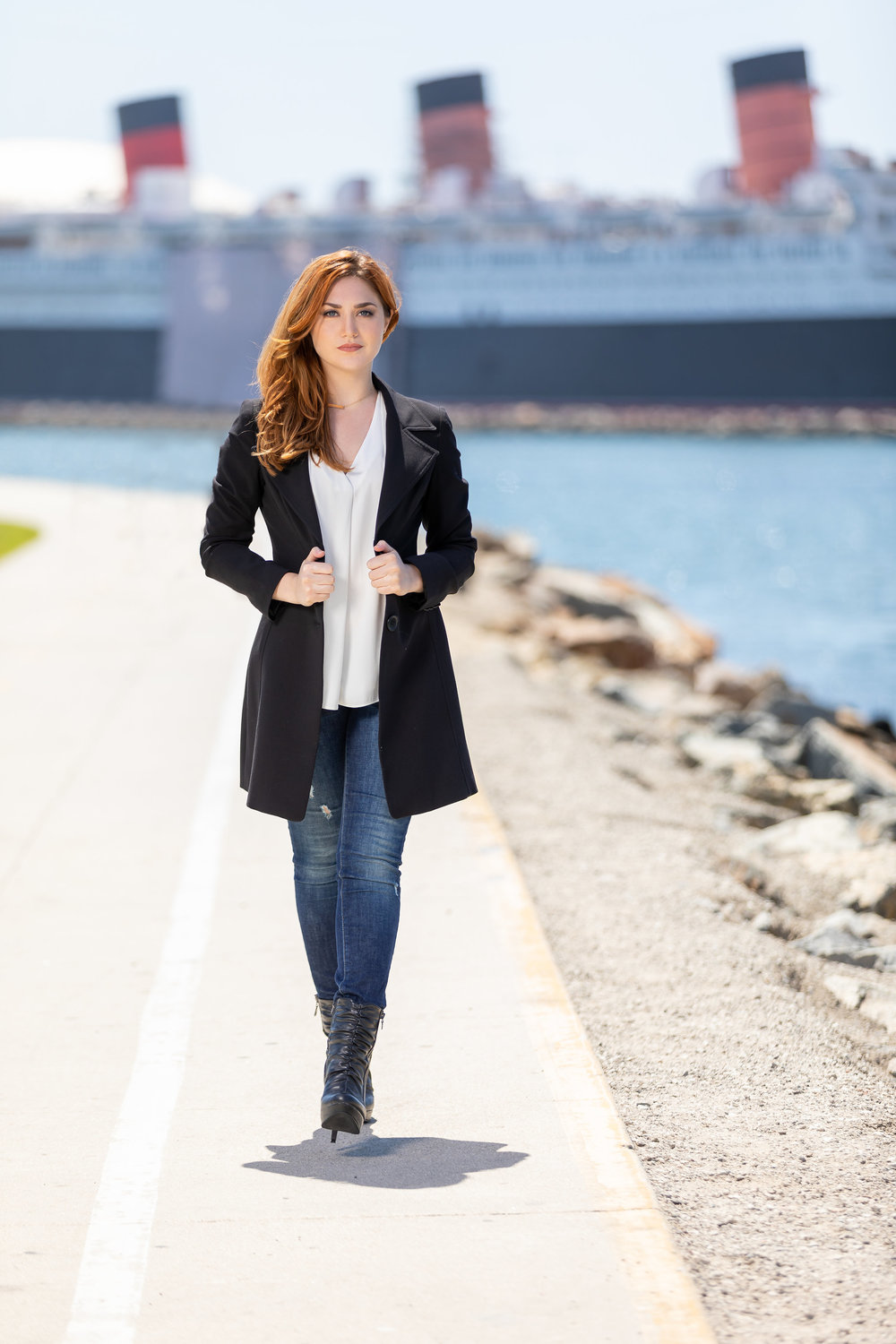High Fashion woman walking along the harbor in a long black jacket jeans and heeled boots.jpg