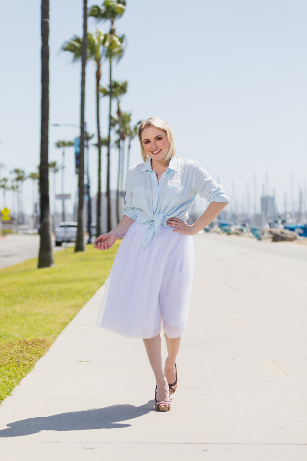 Pretty blonde woman walking down the harbor in heels and a tulle skirt.jpg