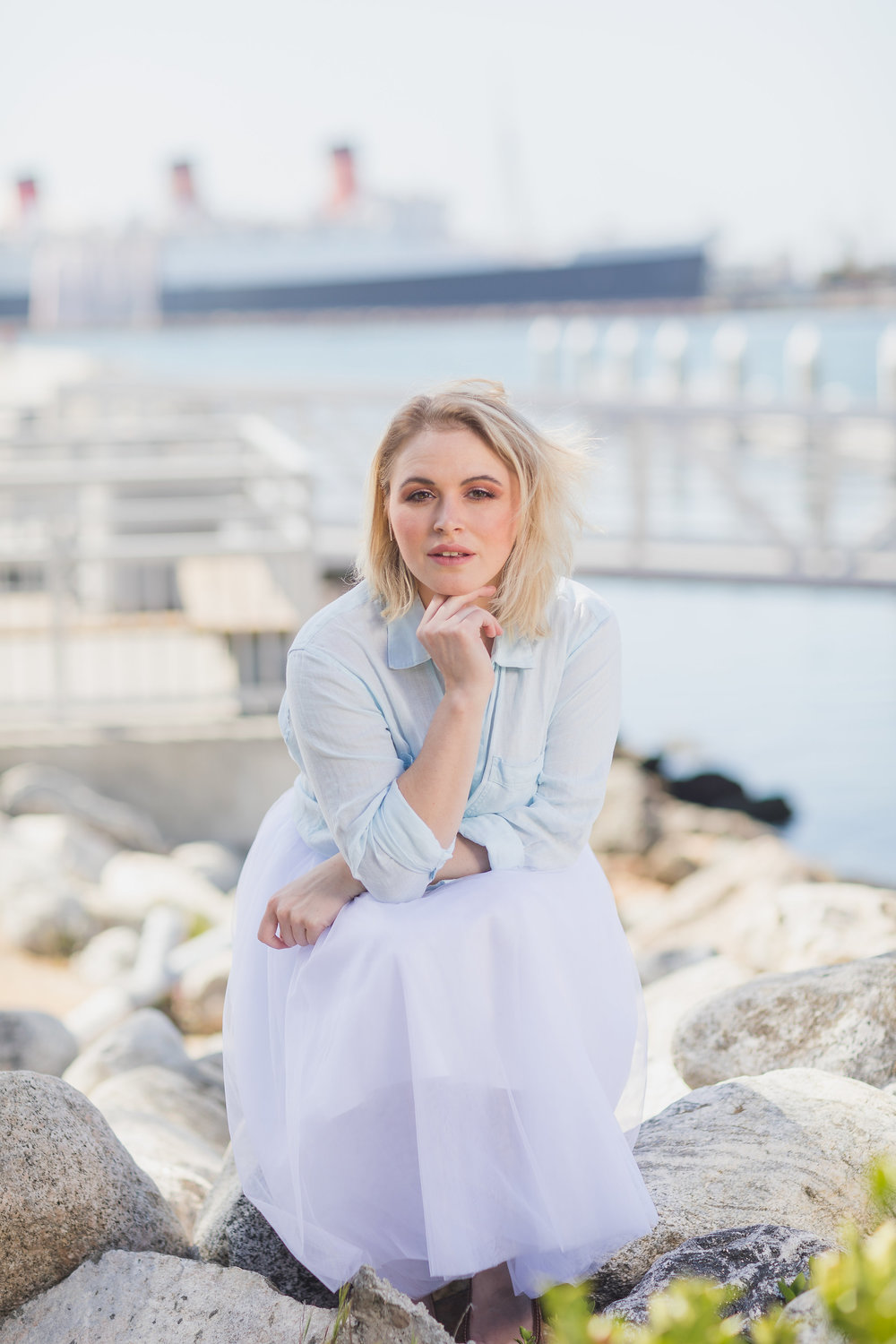 Beautiful edgy female blonde model sitting on the bank of a jetty.jpg