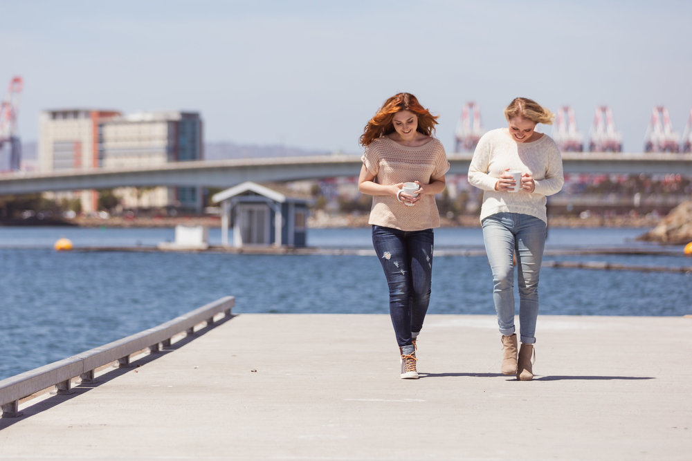 Two women walking along the water on the dock with coffee.jpg