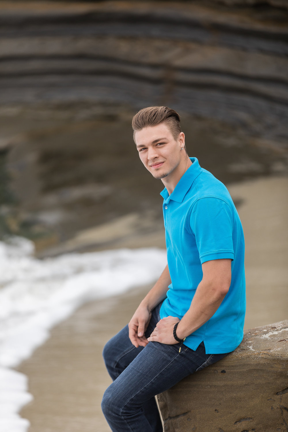 good looking young man sitting on a beach rock in a blue shirt.jpg