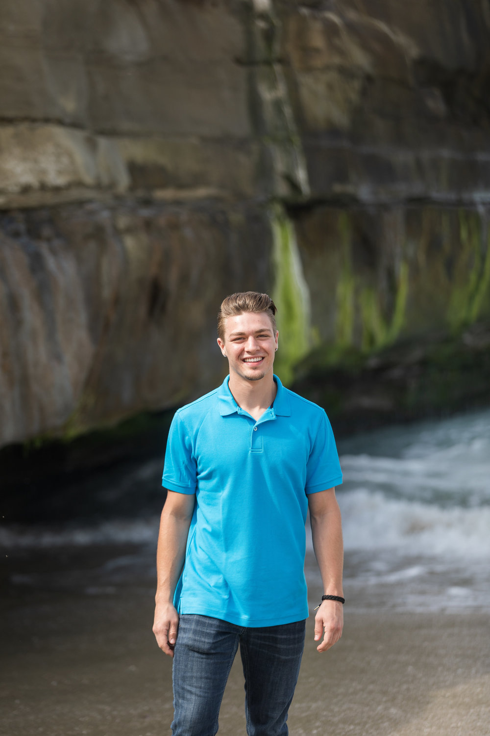 Young adult male in blue shirt on rocky shoreline.jpg