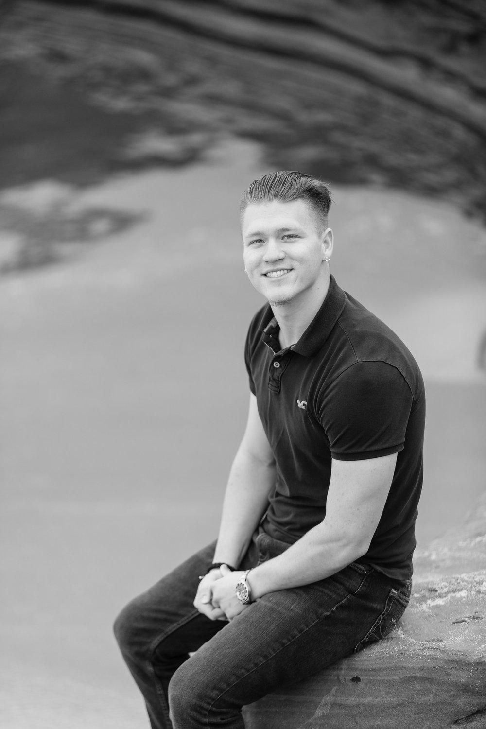 Handsome young adult male sitting on a rock in black and white.jpg