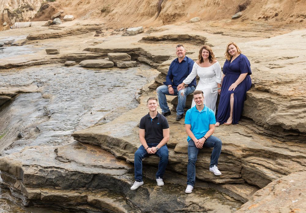 Family Beach Portrait on the rocks in shades of blue and white.jpg